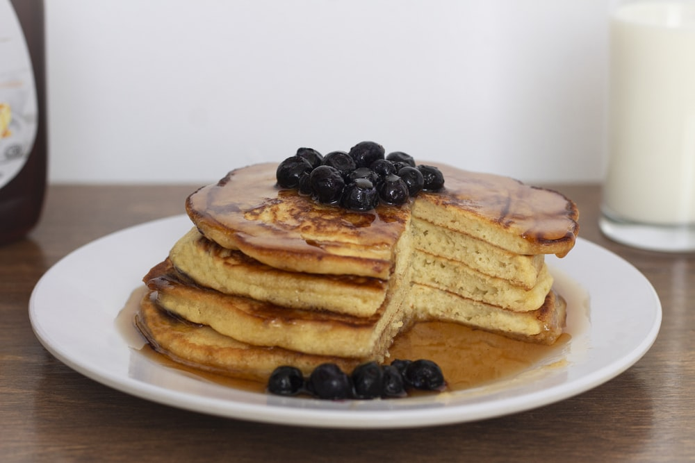 pancakes with black berries on white ceramic plate
