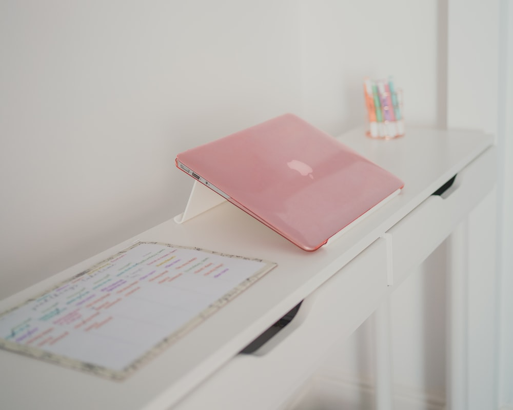 pink laptop computer on white table
