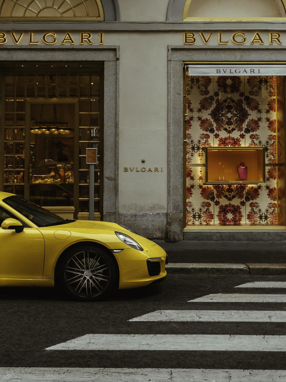 yellow ferrari 458 italia parked beside white concrete building