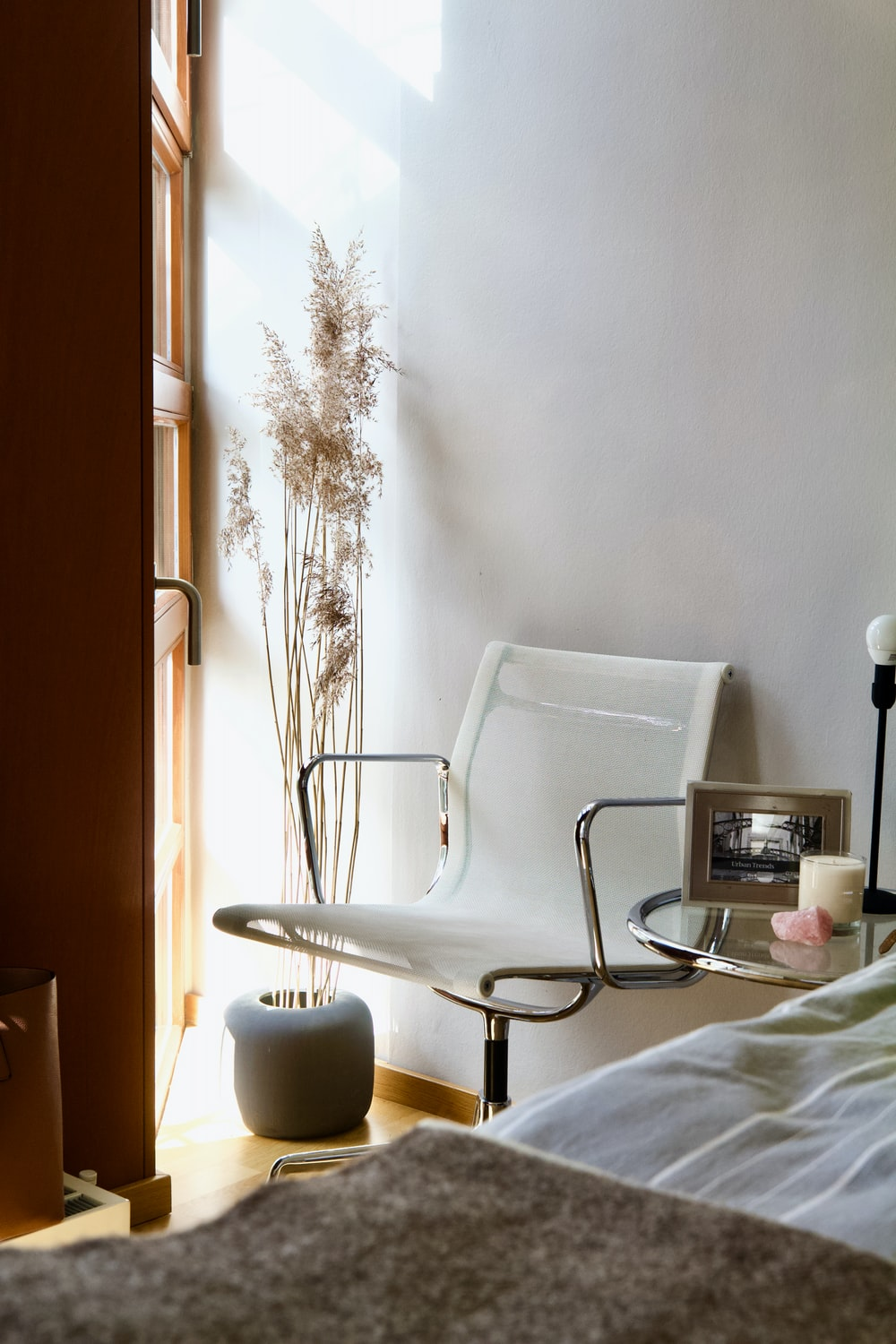 white and black armchair beside white wall