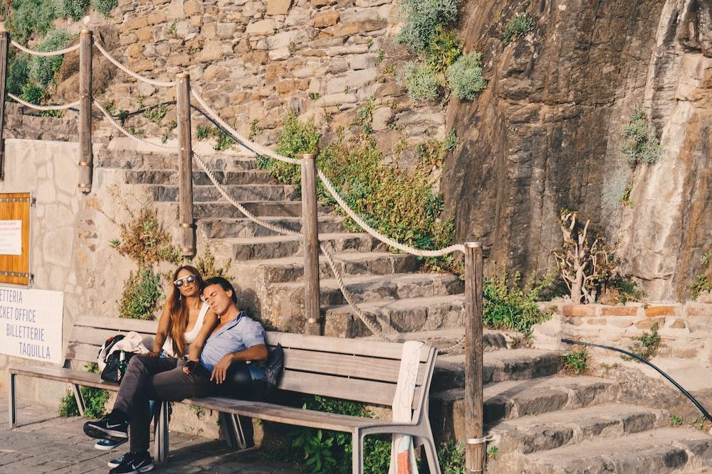 2 women sitting on brown wooden bench during daytime