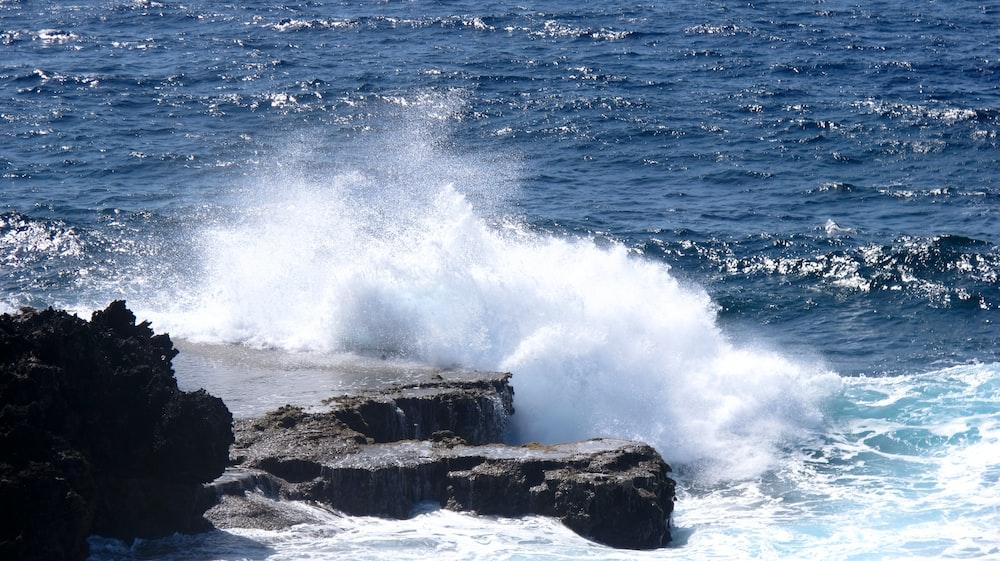 ocean waves crashing on rock formation during daytime