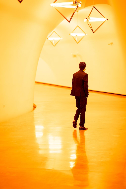 man in black jacket walking on brown wooden floor