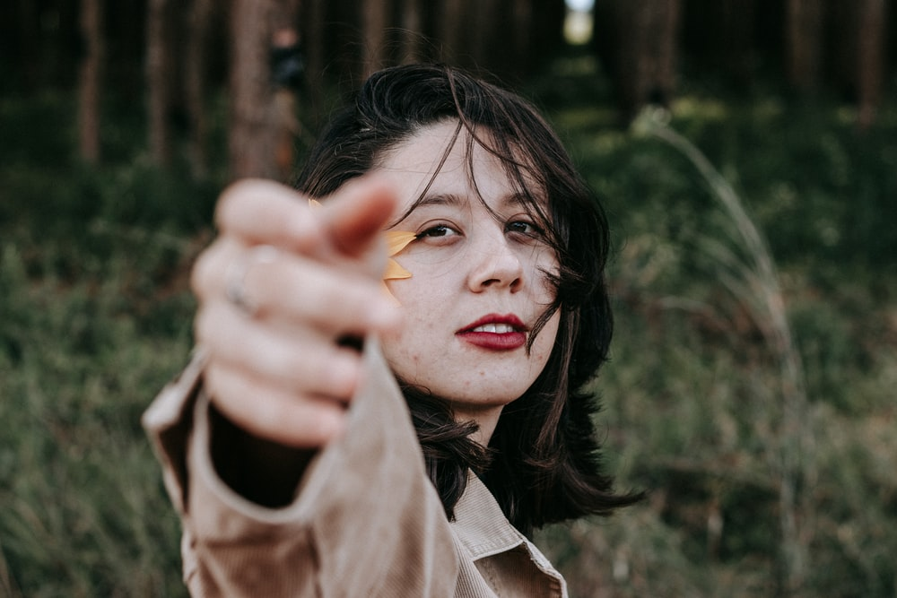 woman in brown jacket holding yellow leaf