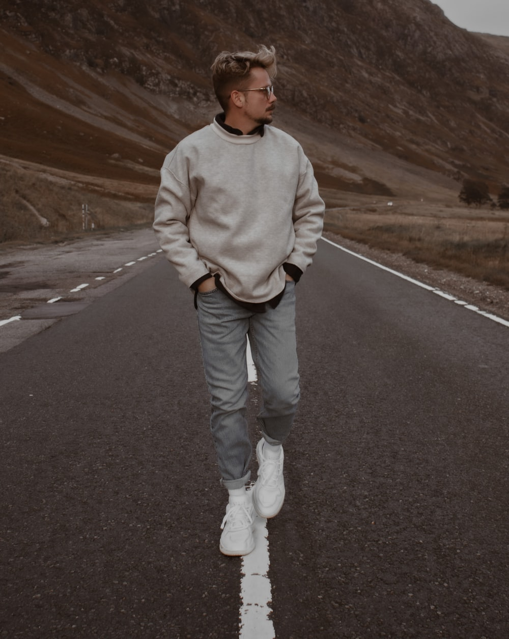man in white sweater and blue denim jeans standing on gray asphalt road during daytime