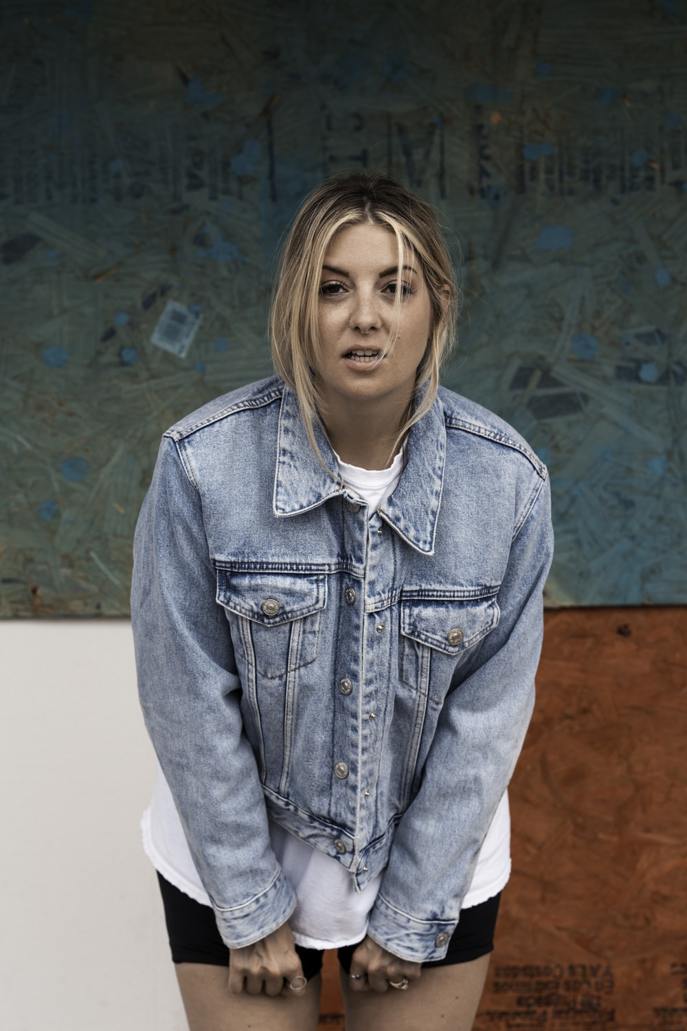 woman in blue denim jacket standing near blue and brown wall