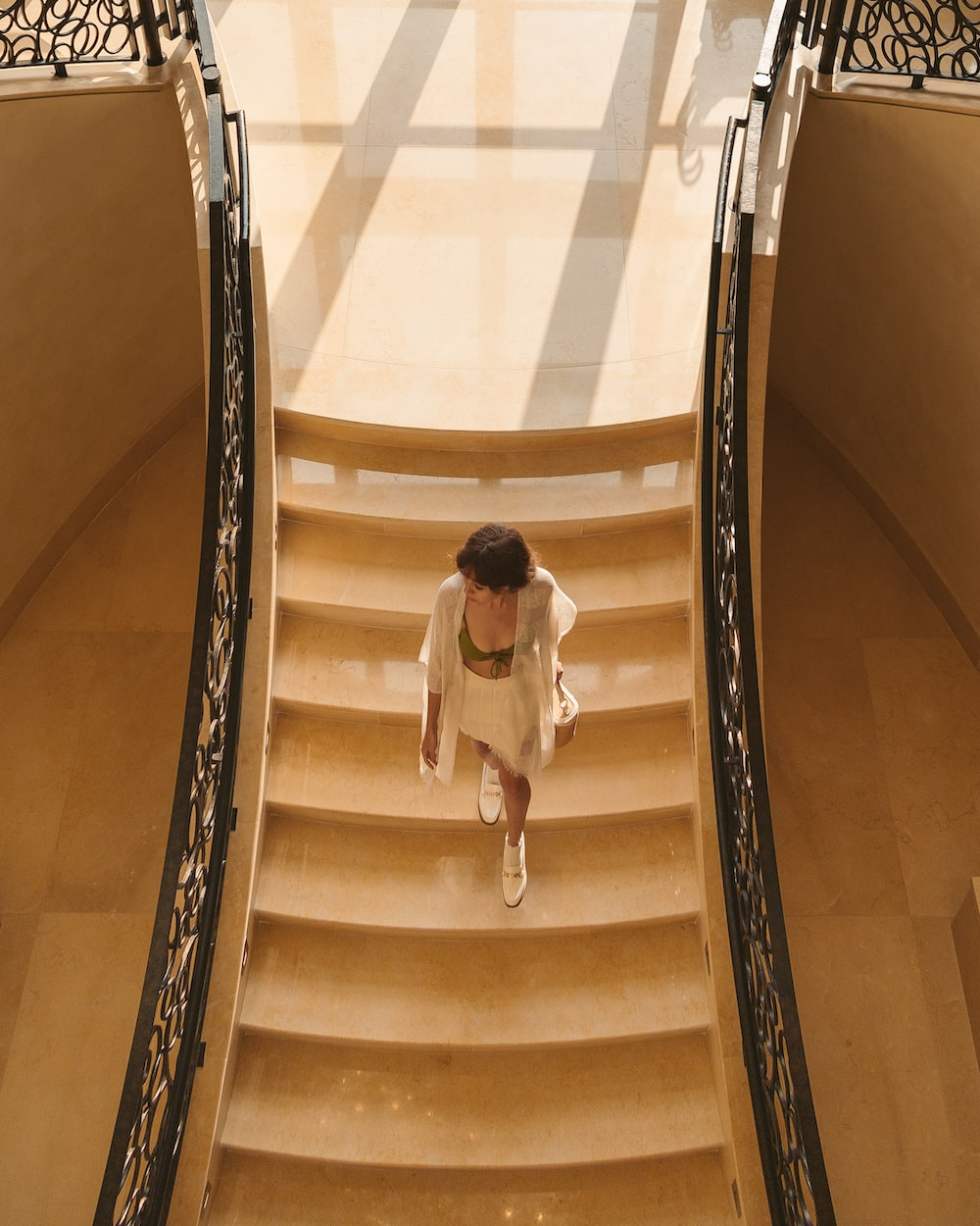 woman in white shirt and black pants walking down on white staircase