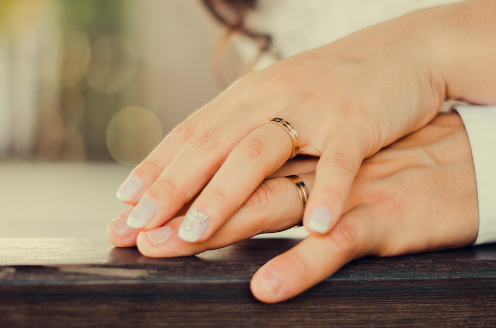 person wearing gold ring on brown wooden table