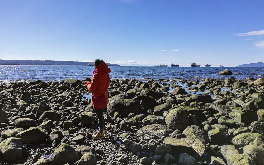 woman in red jacket and black pants standing on rocky shore during daytime
