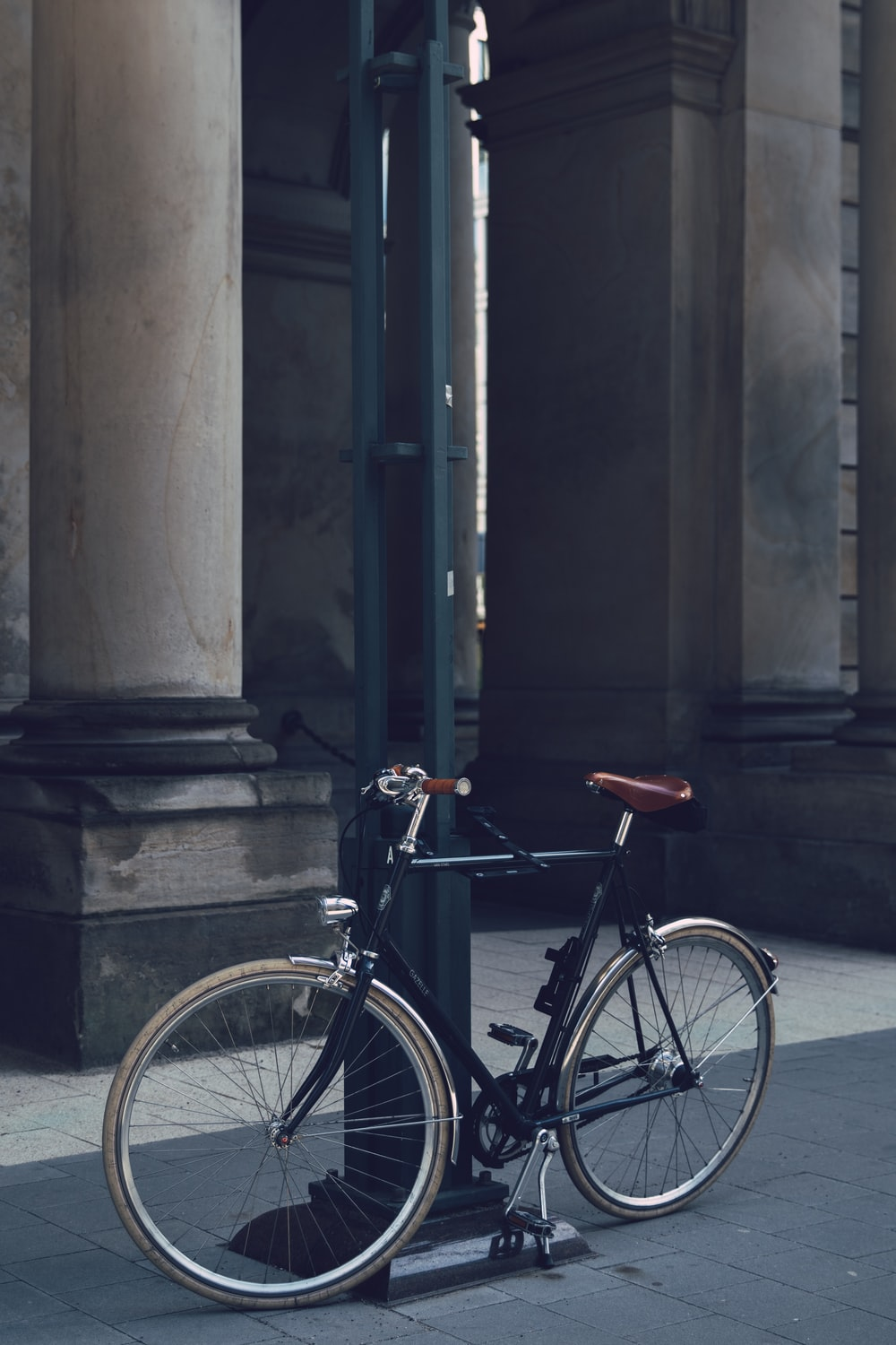 black city bike parked beside gray concrete building during daytime