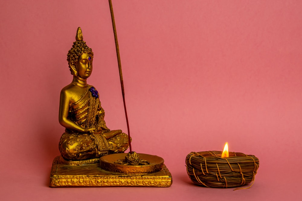 gold buddha figurine beside lighted candles