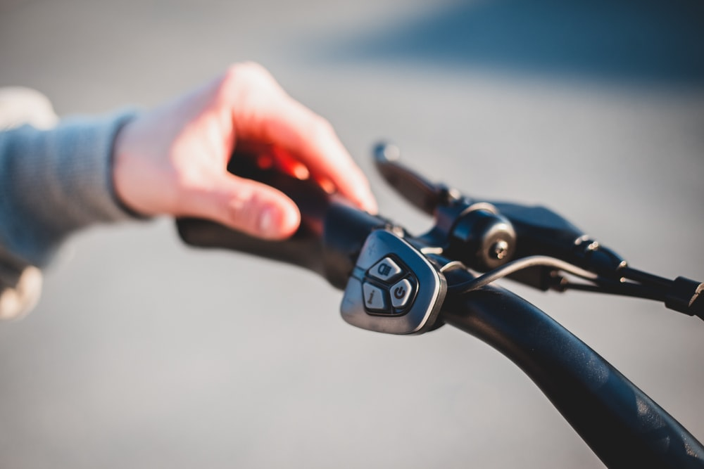 person holding black bicycle handle bar