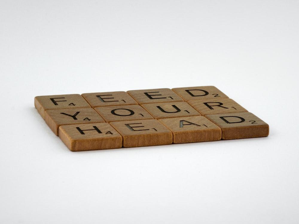 brown wooden letter blocks on white surface