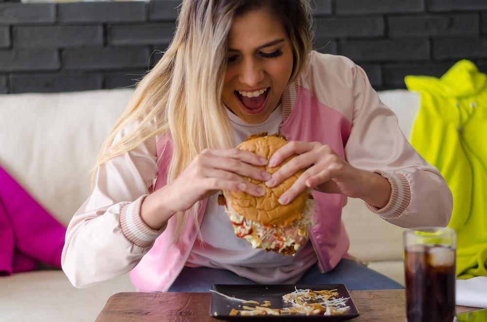 girl in pink long sleeve shirt eating bread