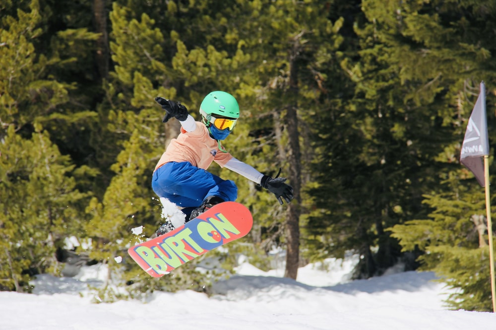 man in blue jacket and red helmet riding red snowboard on snow covered ground during daytime