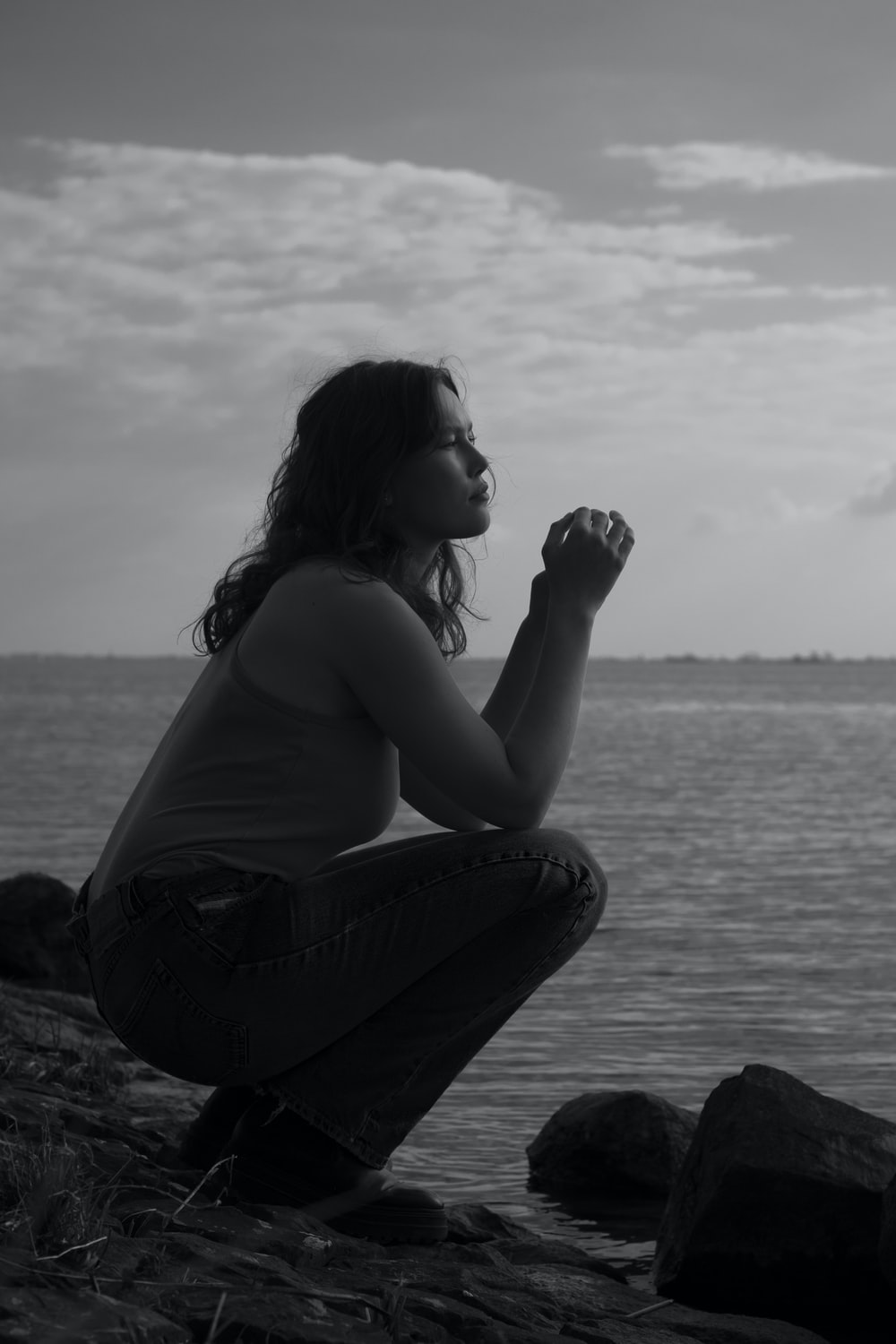 woman in black tank top and blue denim jeans sitting on rock near body of water
