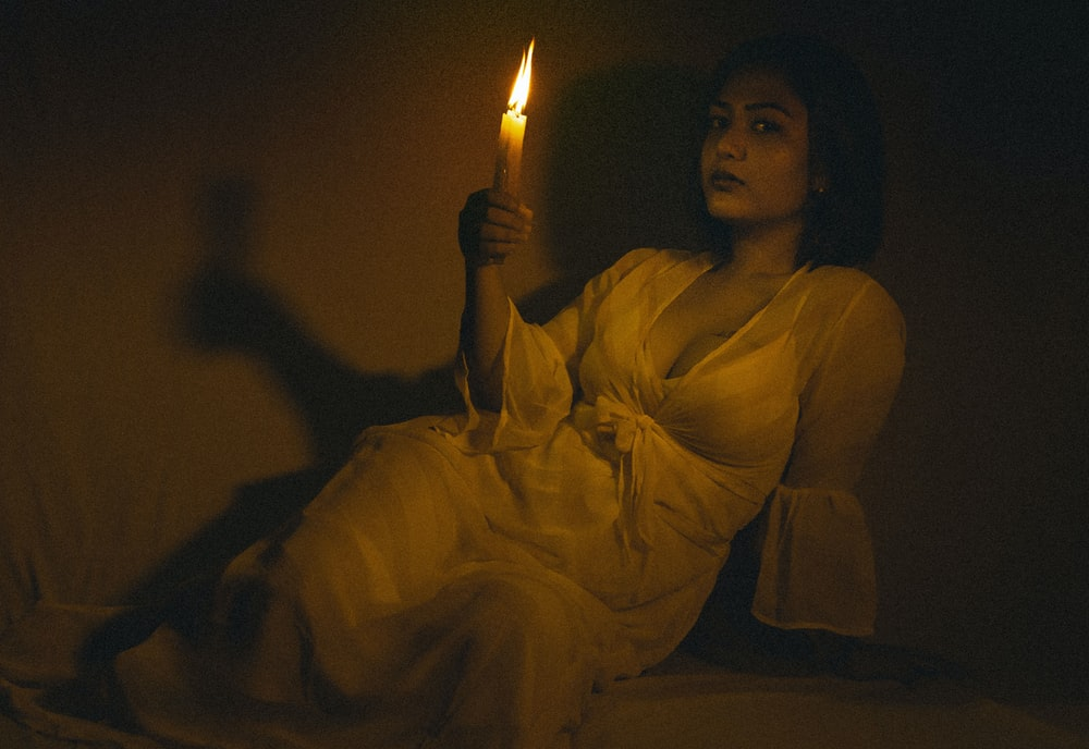 woman in white dress holding lighted candle