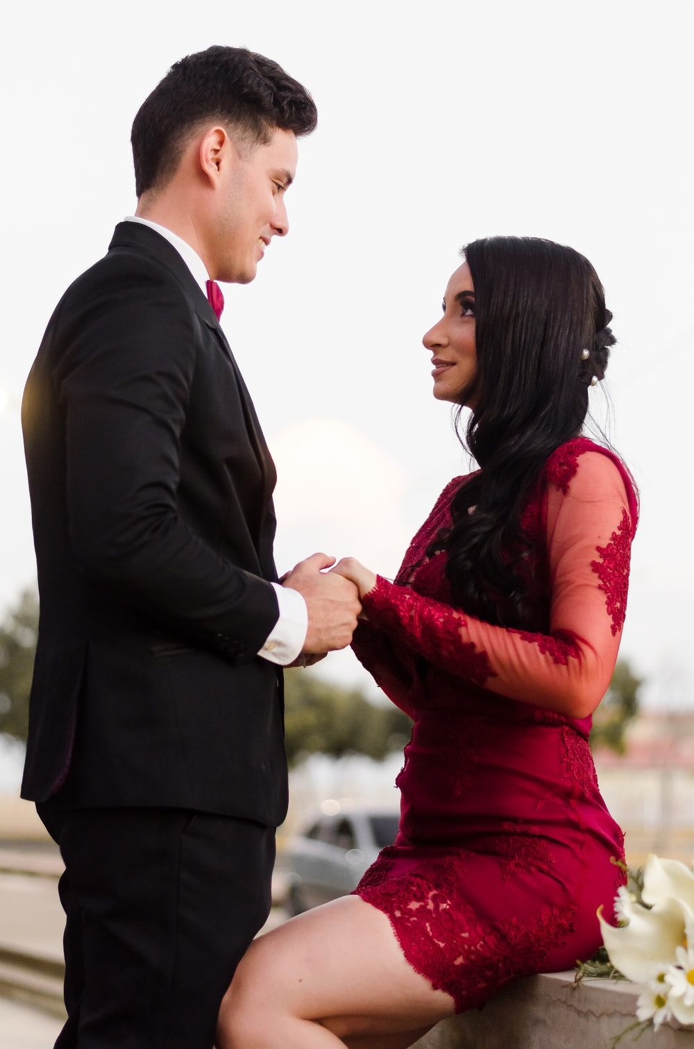 man in black suit jacket kissing woman in red dress
