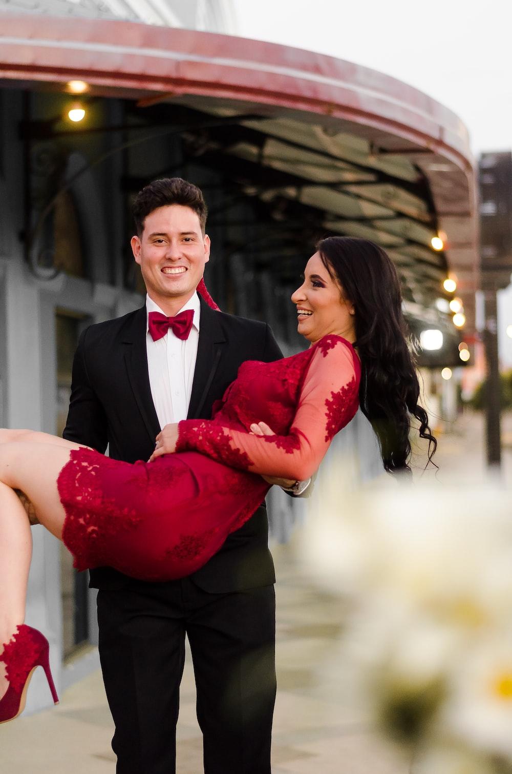 man in black suit hugging woman in red dress