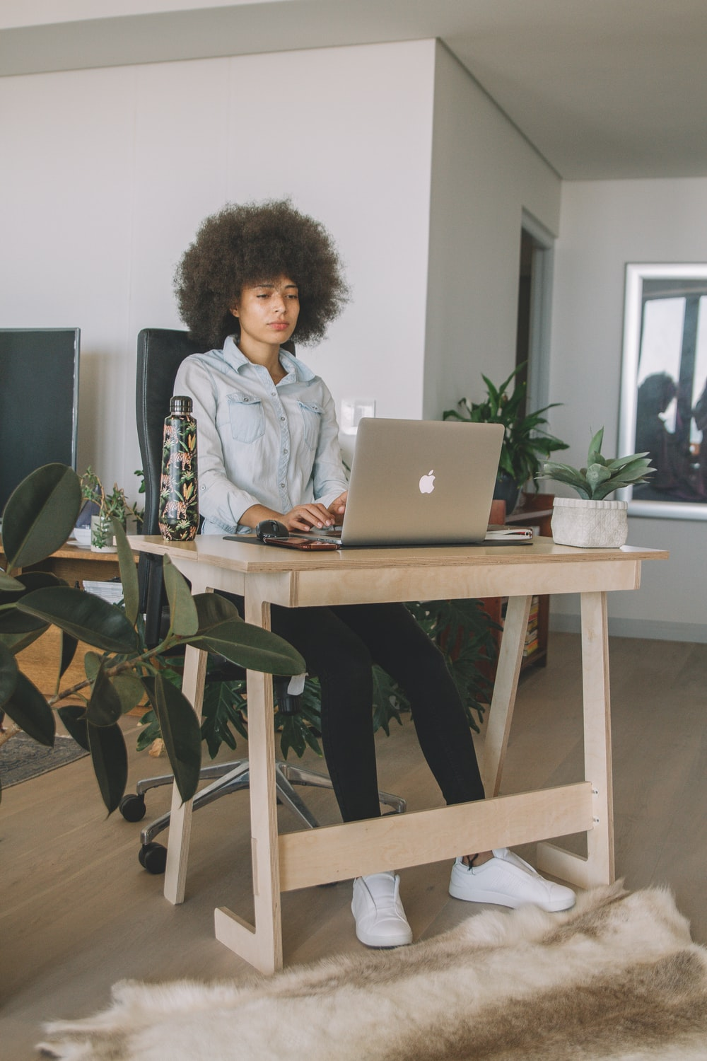 woman in gray jacket sitting on chair using macbook