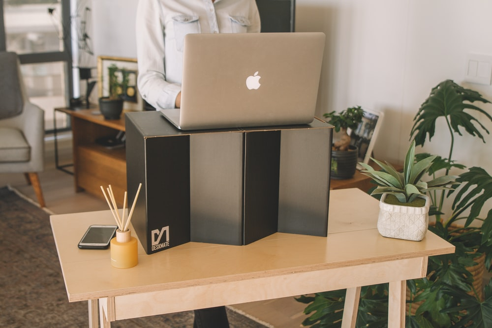 silver macbook on black and white wooden shelf