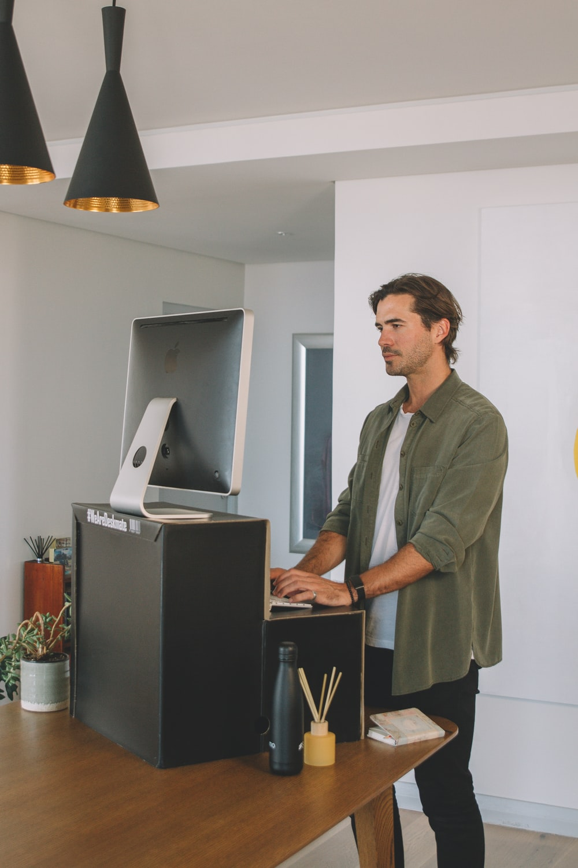 man in gray button up shirt standing near black flat screen computer monitor
