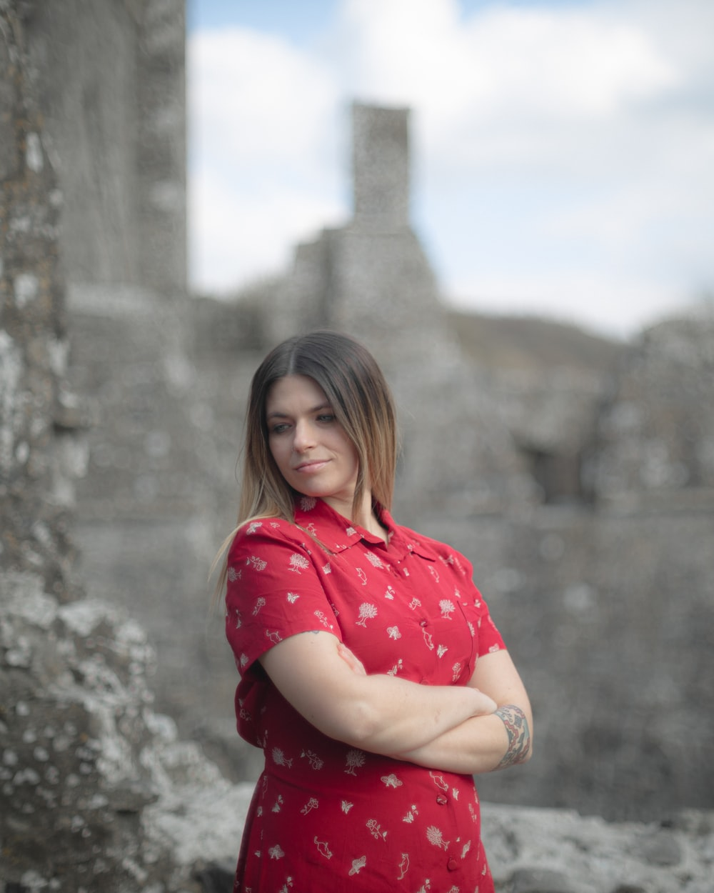 woman in red and white polka dot shirt sitting on rock