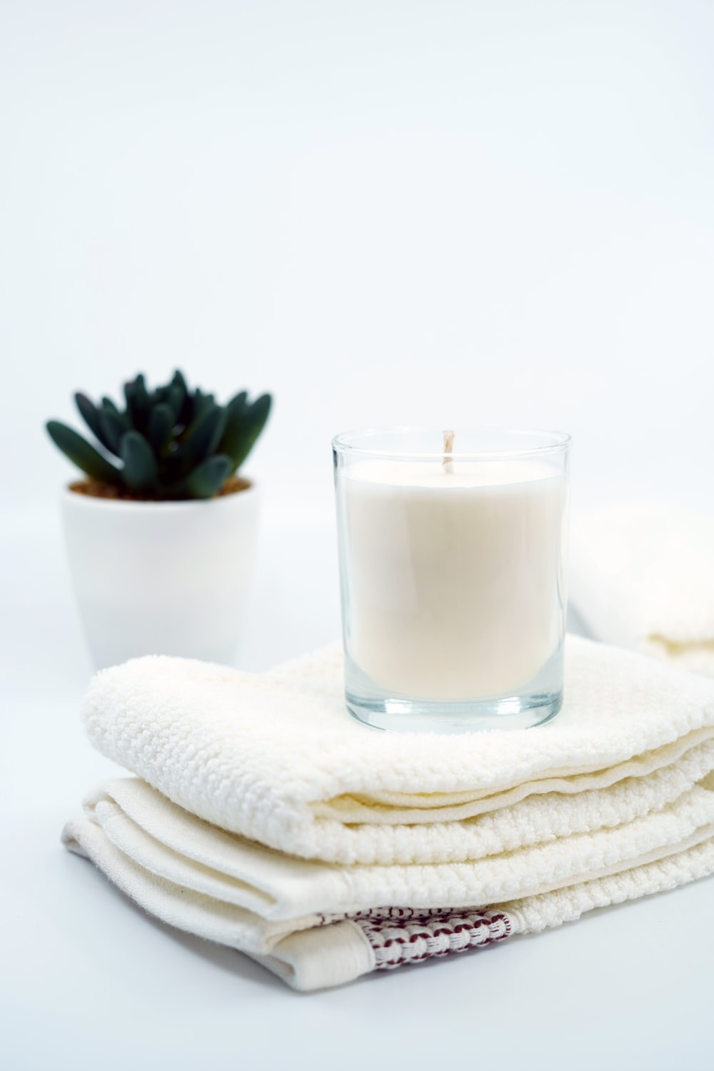 white pillar candle on clear glass candle holder