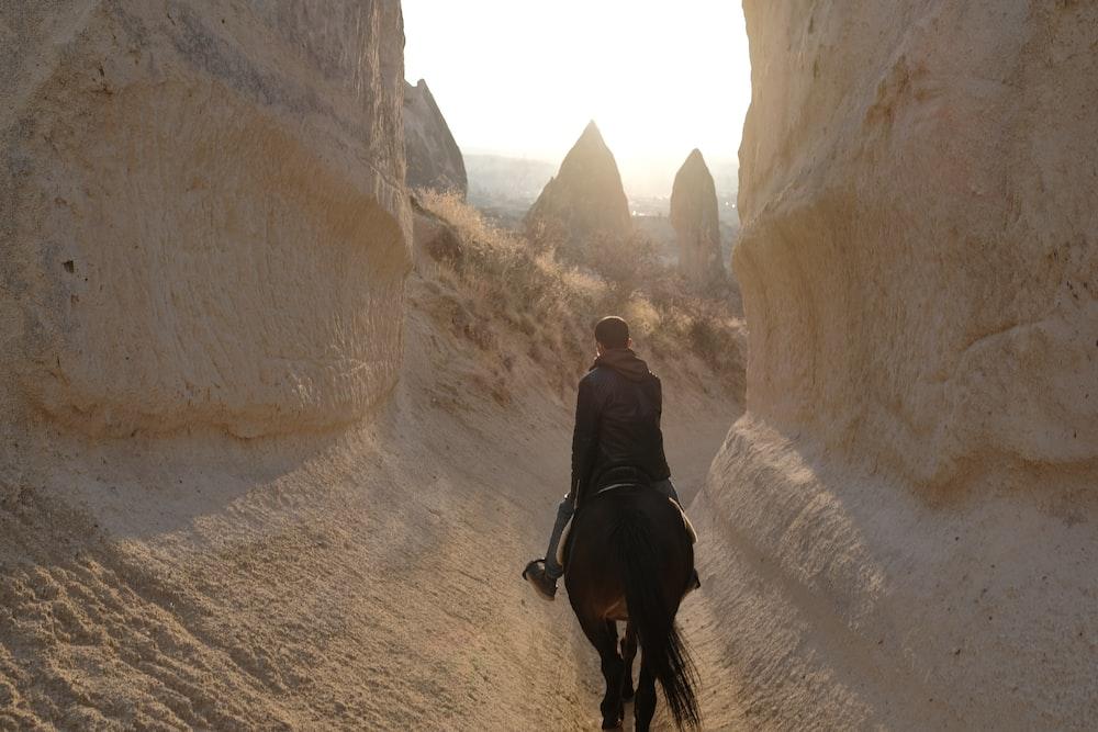 man in black jacket walking on brown dirt road during daytime