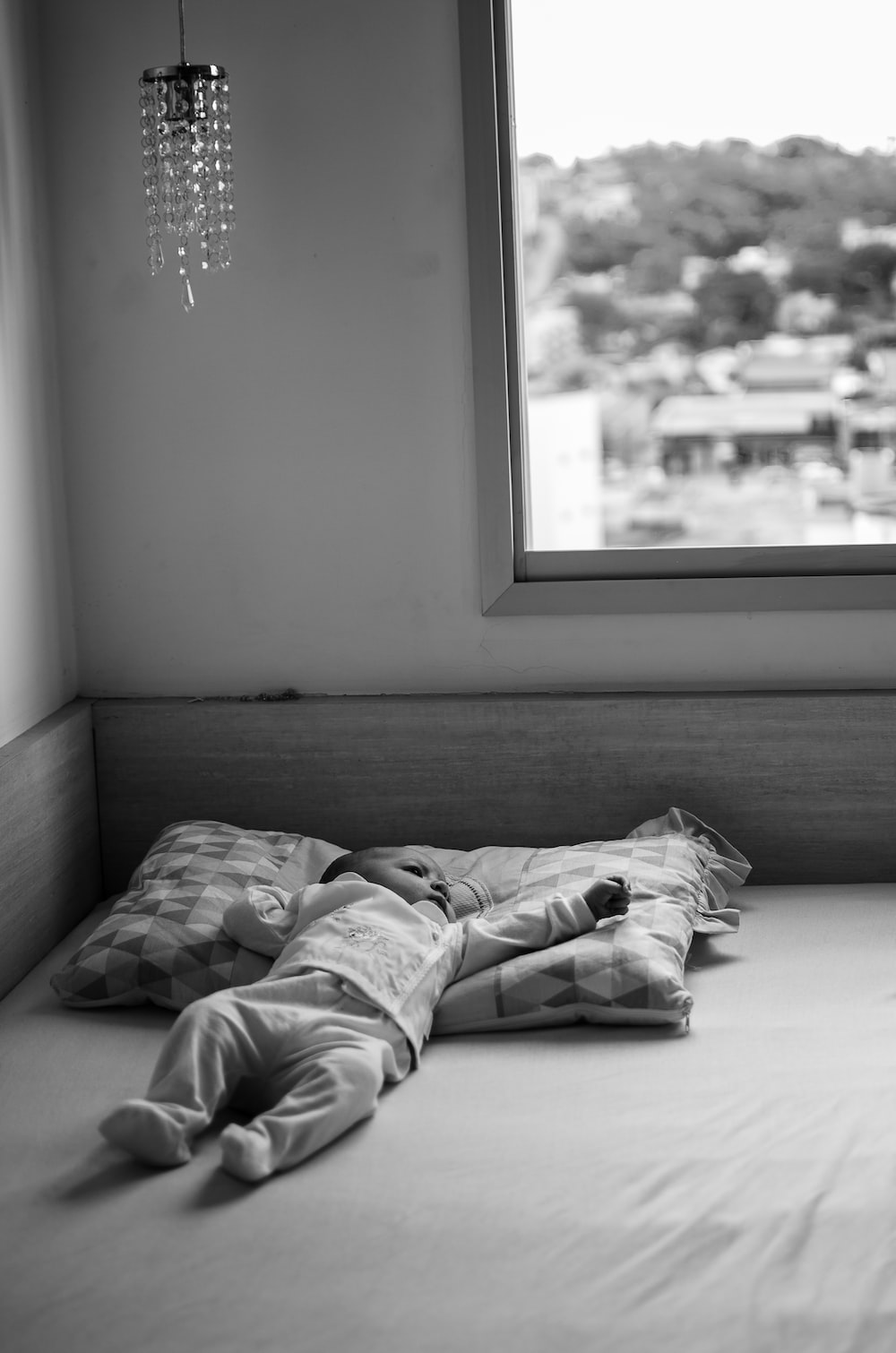 grayscale photo of person lying on bed
