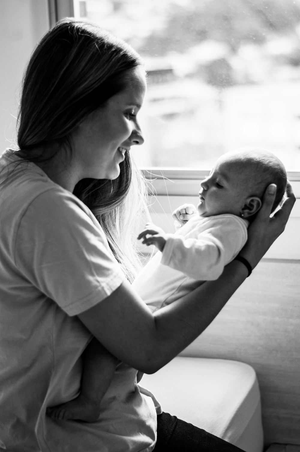 grayscale photo of woman in t-shirt carrying baby