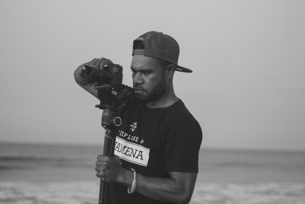 man in black crew neck t-shirt holding black microphone