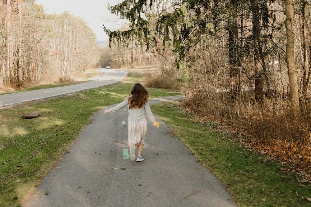 girl in white shirt walking on gray asphalt road during daytime