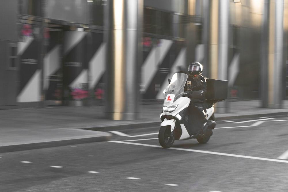 man in black jacket riding white motorcycle on road during daytime