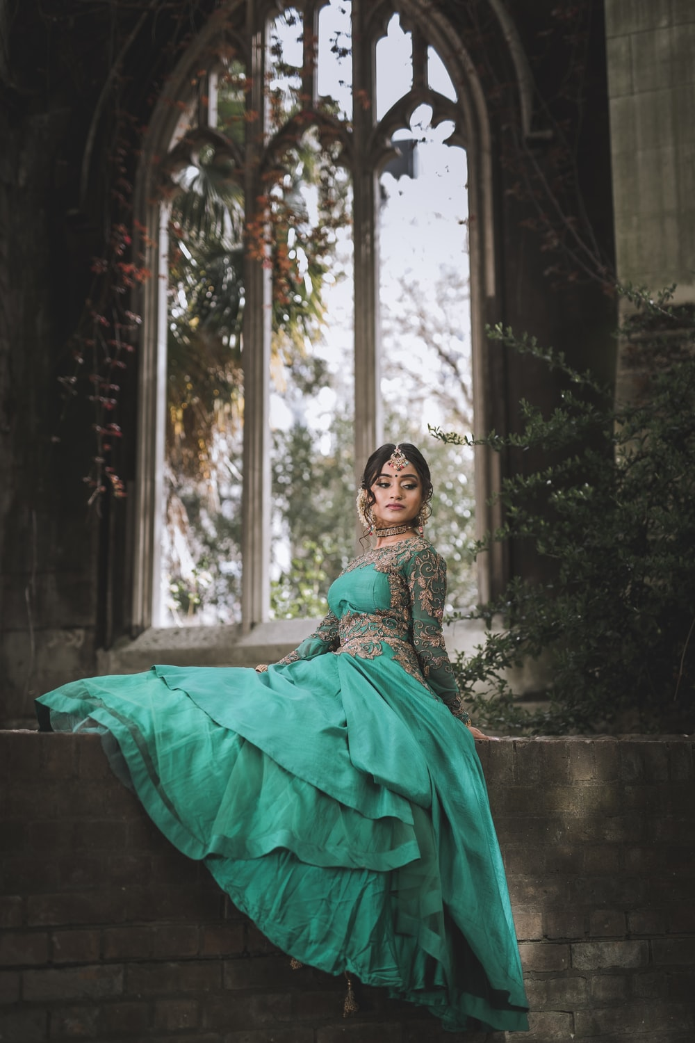woman in green dress sitting on concrete bench