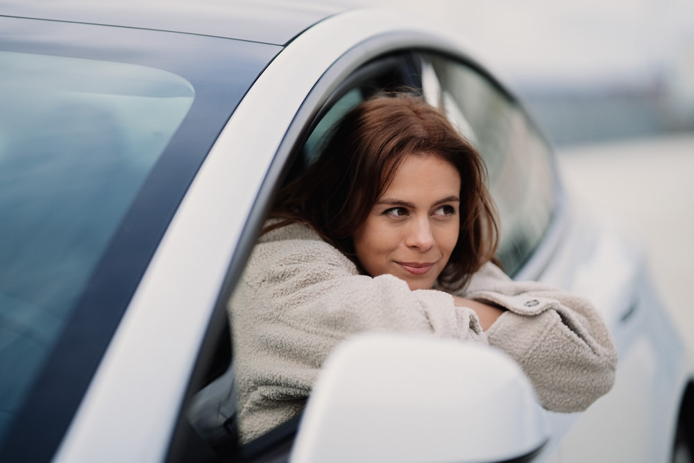 woman in gray coat leaning on white car