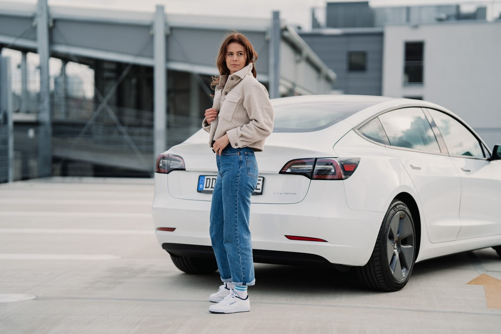 woman in white jacket and blue denim jeans standing beside white car during daytime