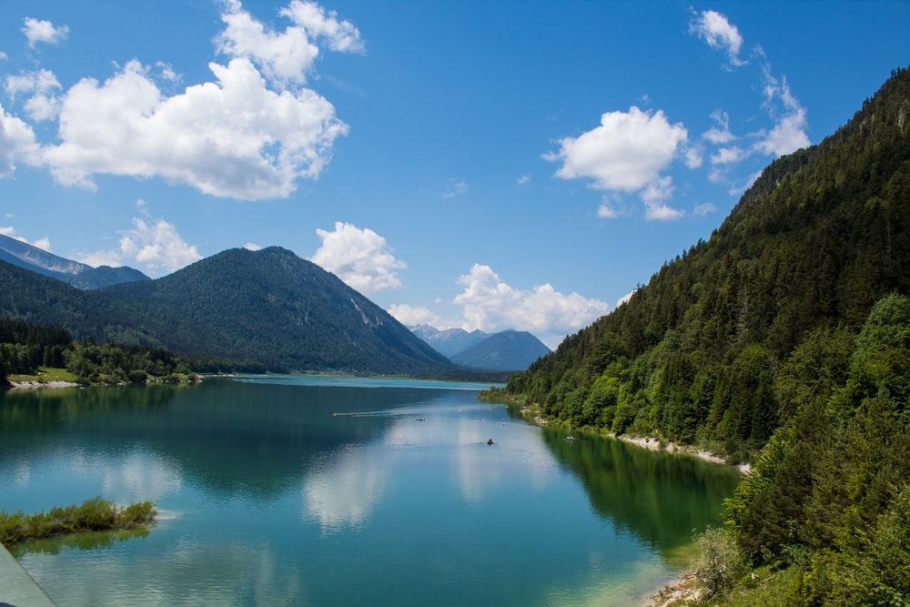 lake surrounded by green trees and mountains under blue sky and white clouds during daytime
