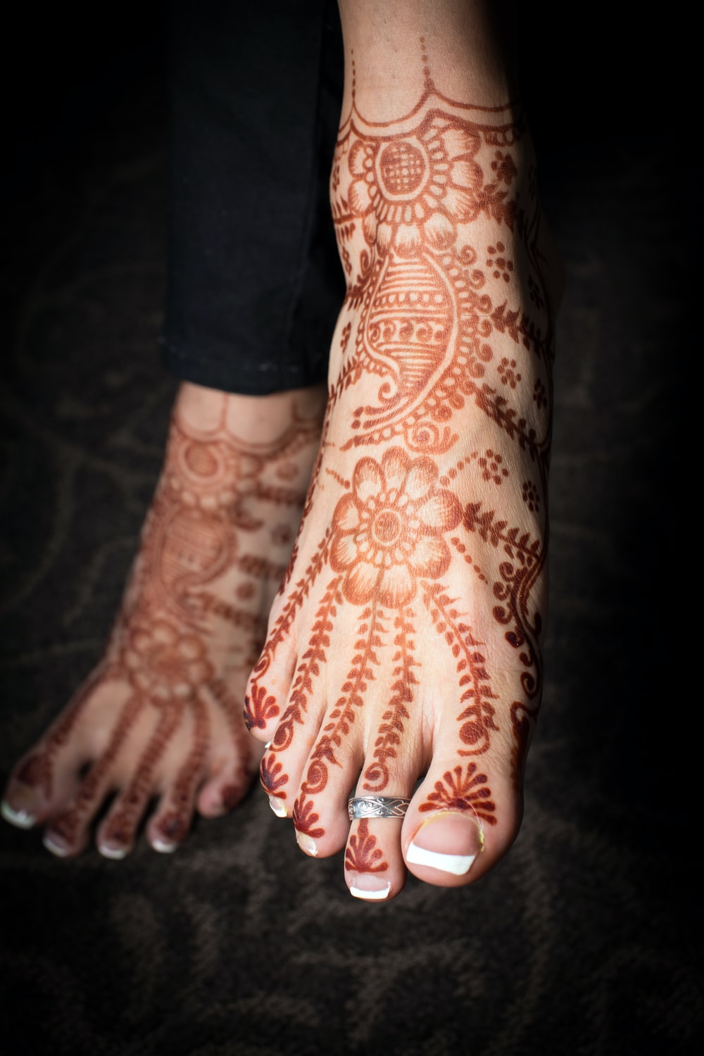 person with red and white floral tattoo on left hand