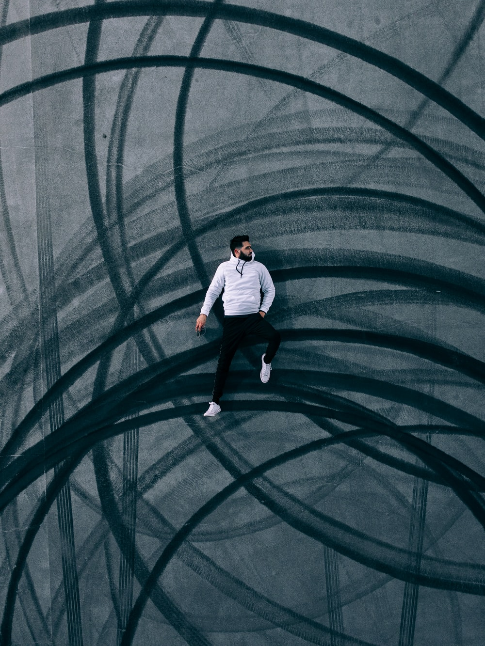 man in white shirt and black pants standing on green tunnel