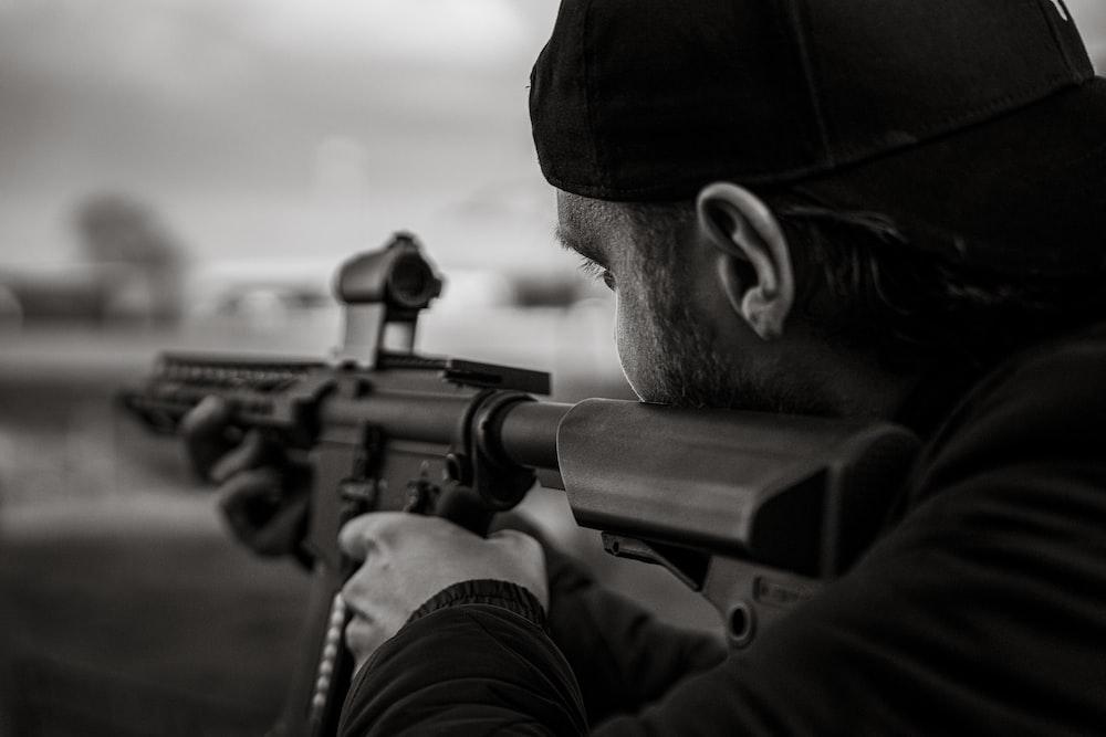 man in black knit cap holding rifle