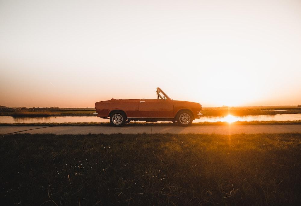 orange car on brown field during sunset