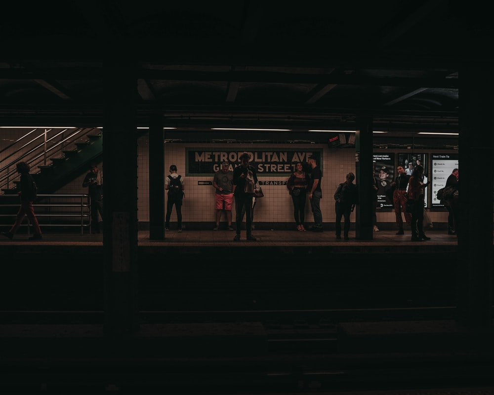 people standing on a train station