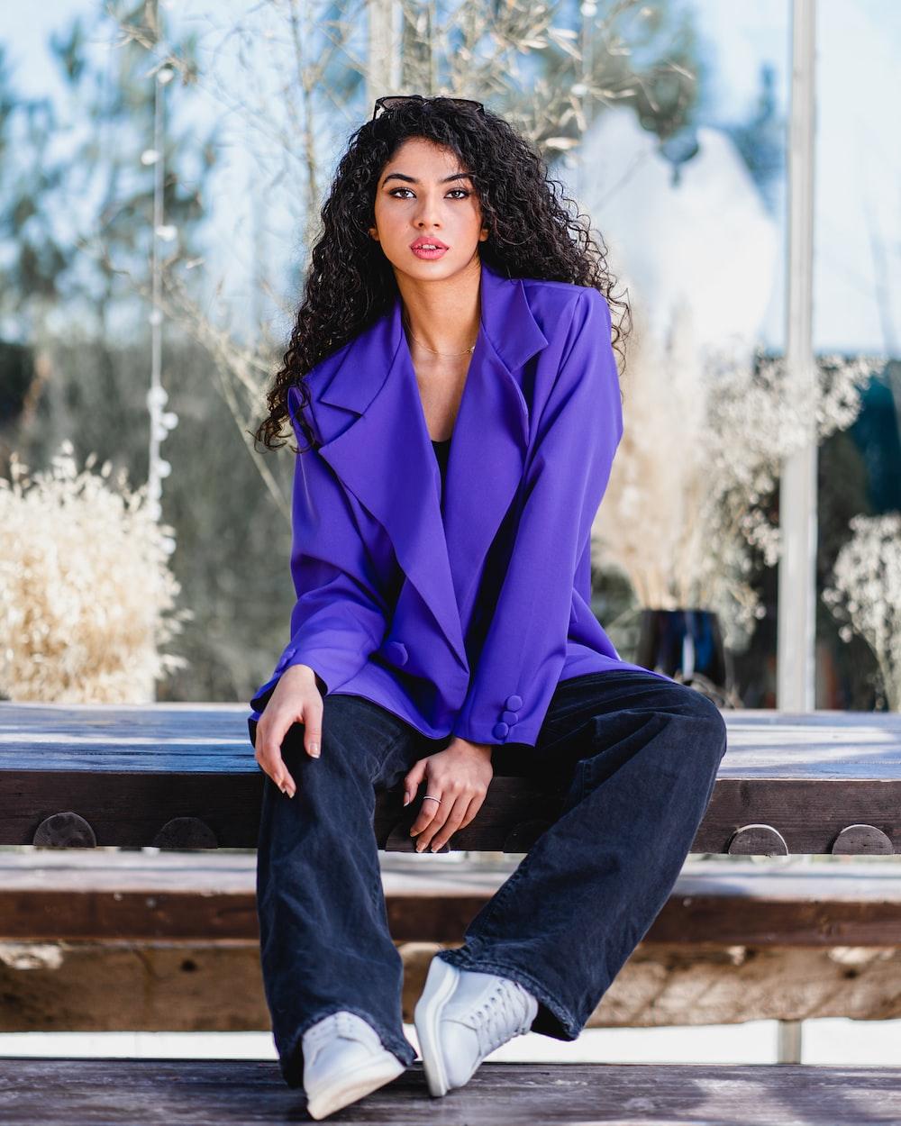 woman in purple blazer sitting on brown wooden bench during daytime