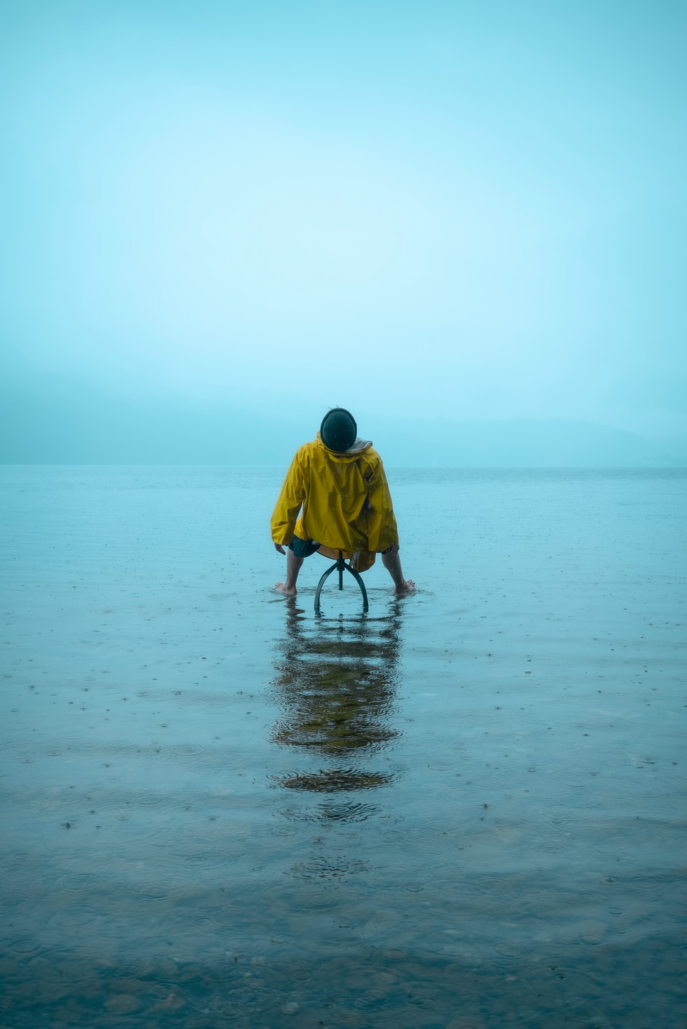 man in yellow hoodie walking on beach during daytime