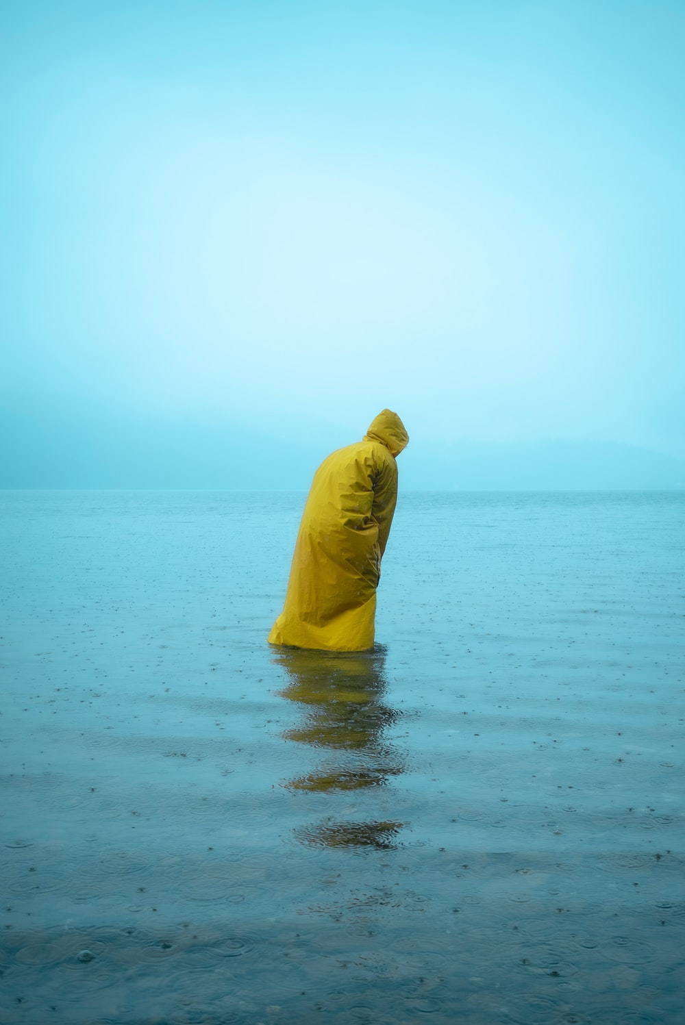 person in yellow hoodie standing on sea shore during daytime