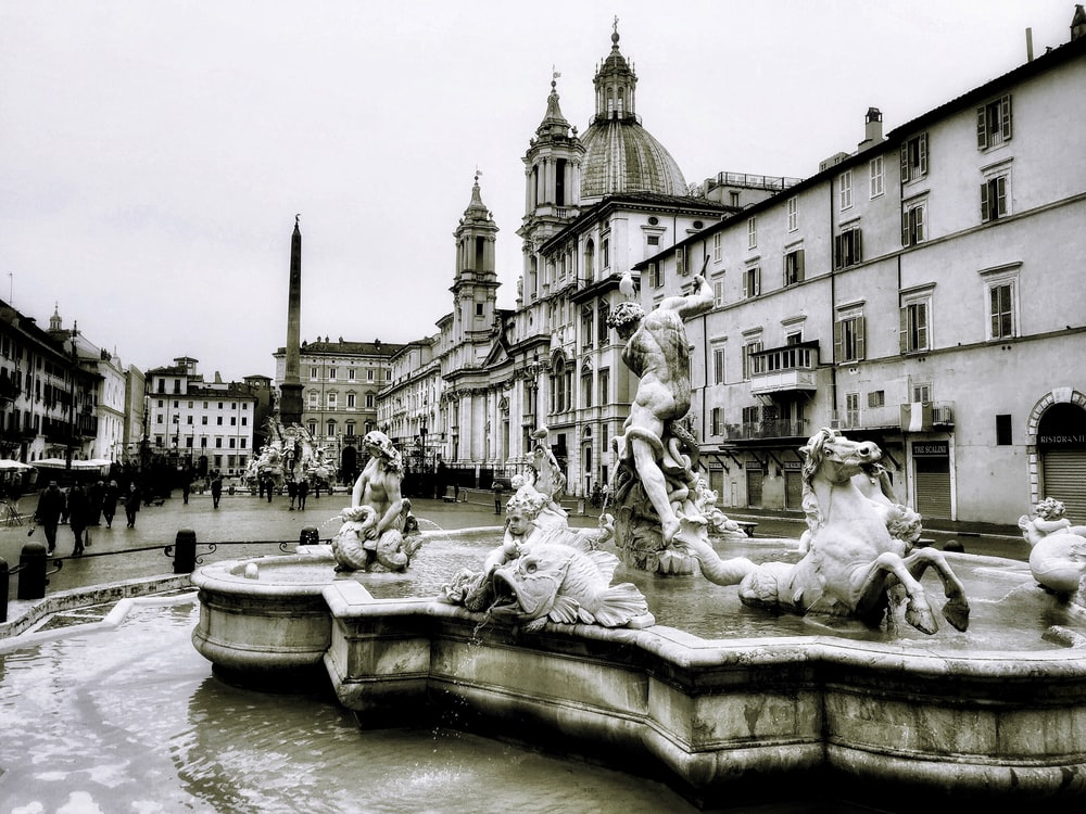 grayscale photo of fountain in the middle of the city