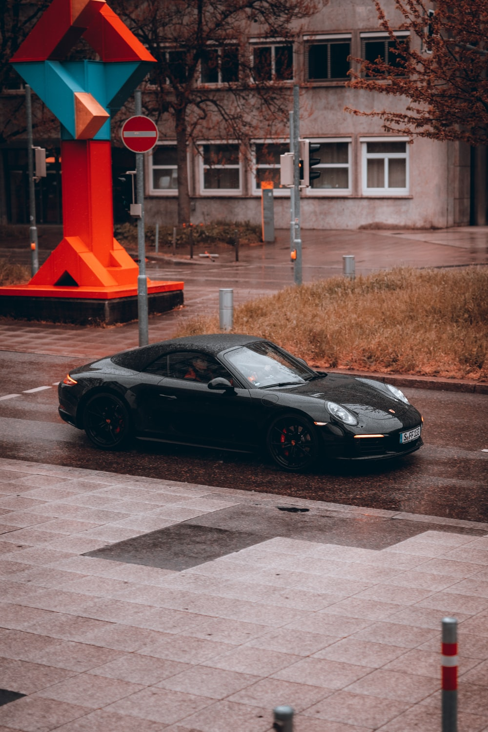 black porsche 911 parked beside red and white building