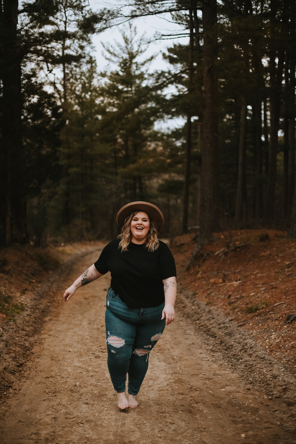 woman in black t-shirt and blue denim shorts standing on dirt road between trees during