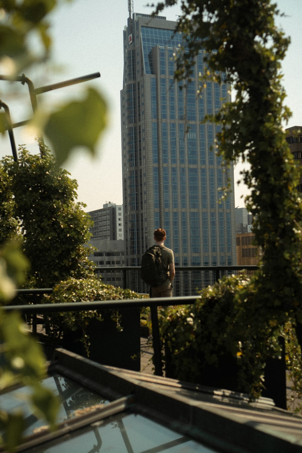 man in gray jacket standing on balcony during daytime